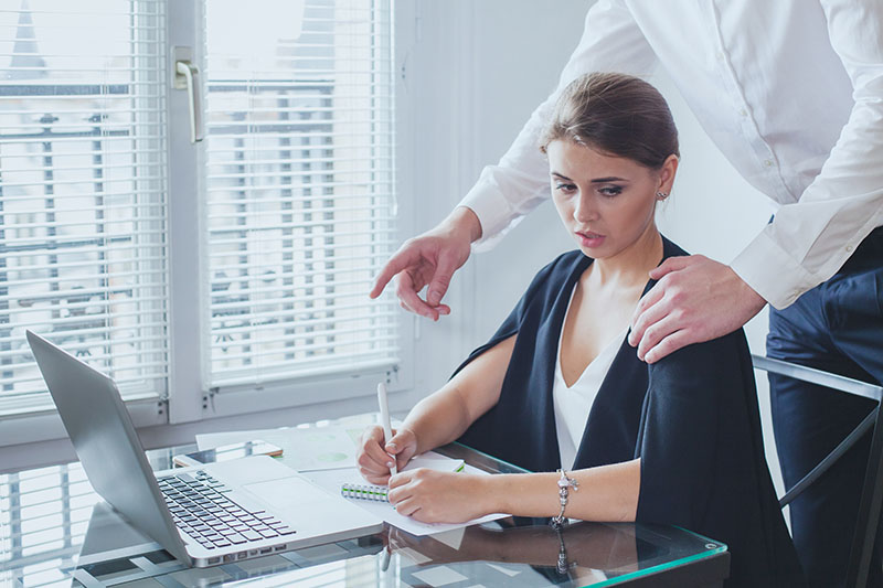 woman in office looking uncomfortably at boss's hand on her shoulder