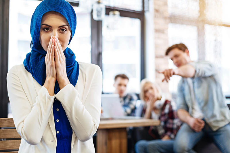 Muslim woman feeling humiliated as coworkers point in the background